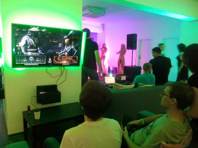 Только настоящие геймеры могут невозмутимо играть в Mortal Kombat, пока на сцене неподалеку зажигают сексуальные девушки